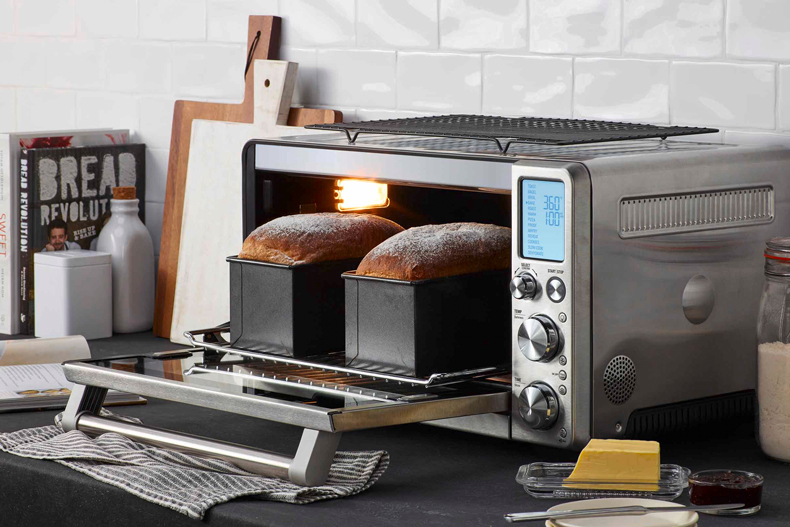 The Smart Oven Air door opening to reveal two loaves of freshly baked bread.