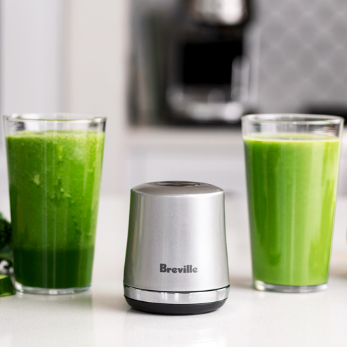 The Vac Q next to two glasses of green smoothie.
