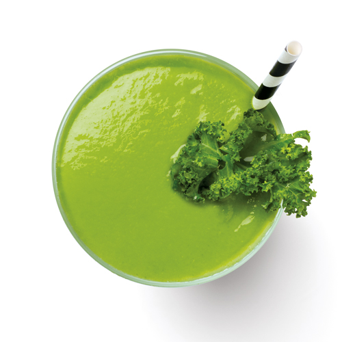 Top view of a green smoothie with fresh kale and straw.