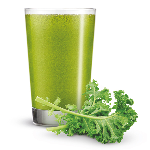 A glass of green smoothie and a piece of fresh kale.