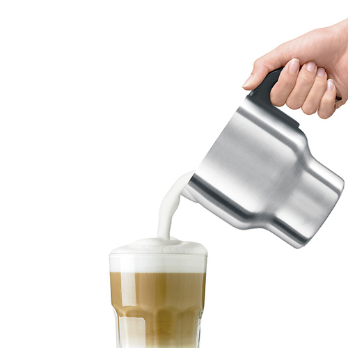 Individual pouring hot chocolate drink from the frother jug into a glass.