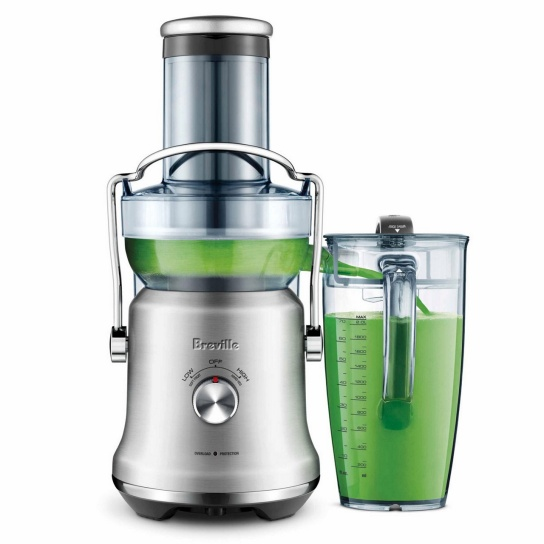 Green juice pouring into juice jug from juicer.