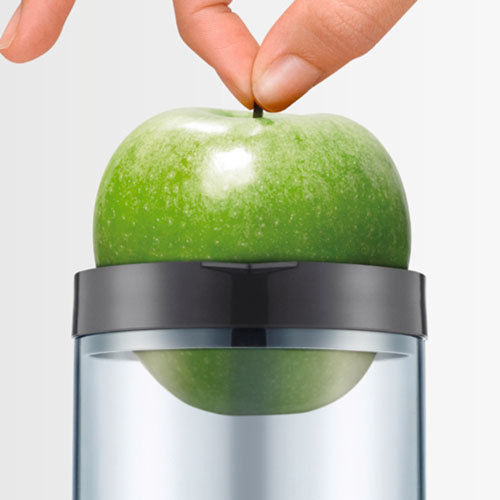 Green apple, that can be juiced whole, going through the wide chute.
