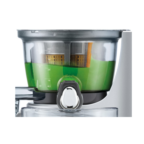 Green juice is being mixed in juicer just before being poured.
