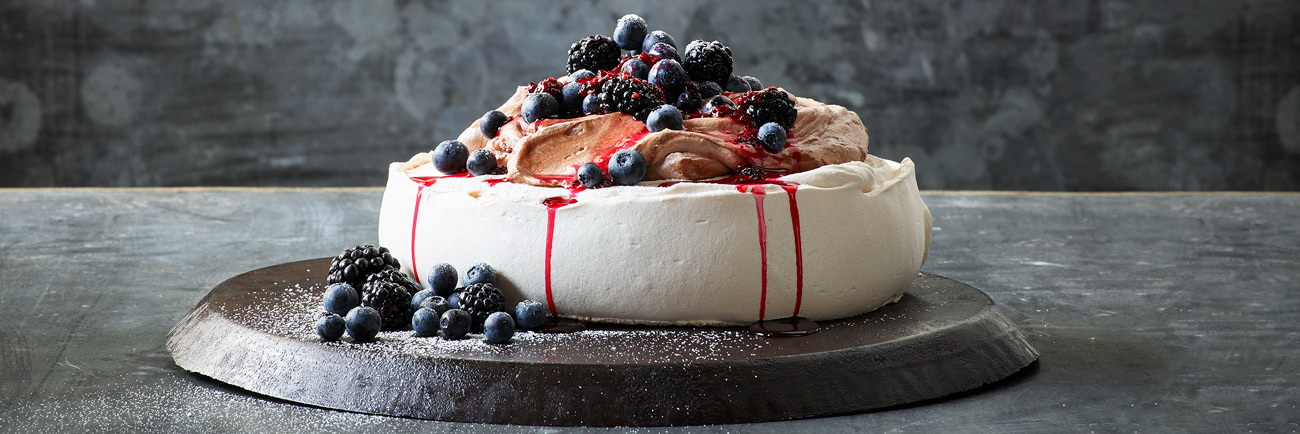 A pavlova with, with fes cream and chocolate mousse topped with fresh berries.