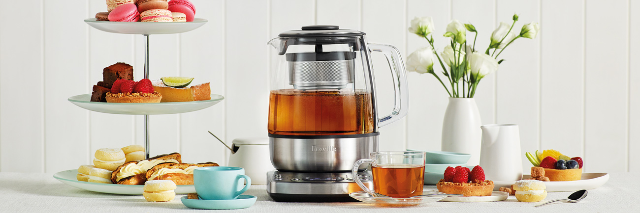 Tea maker with freshly brewed tea accompanied by cups of tea and plates of cakes and cookies.