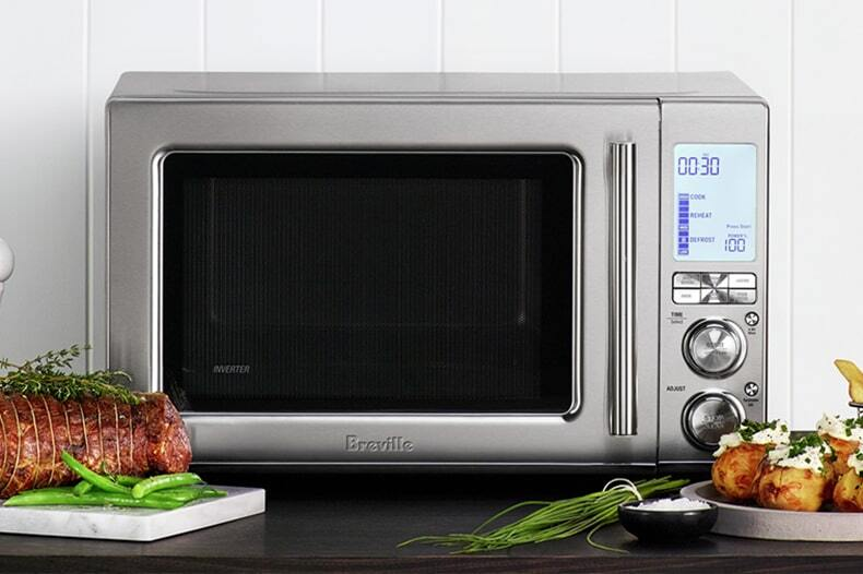 Front view of microwave on a bench with roasted meats, potatoes, chives and sea salt.