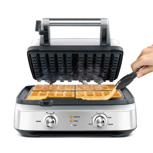 Person removing waffle from waffle maker.